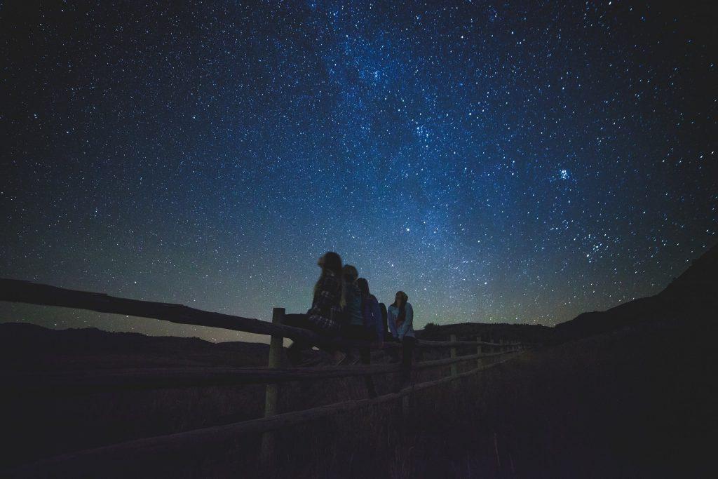 Grupo de pessoas sentadas em uma cerca olhando o céu estrelado.