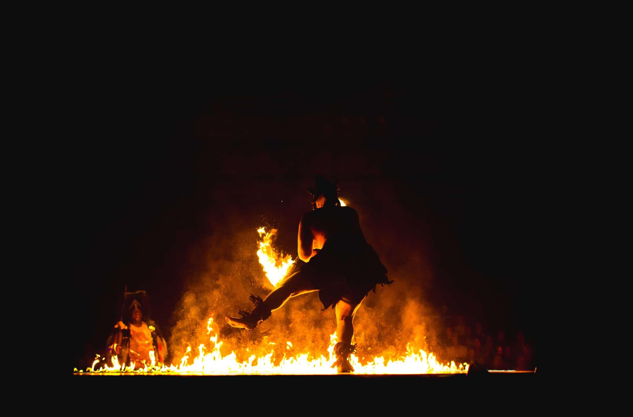 Ritual com homem dançando sobre o fogo