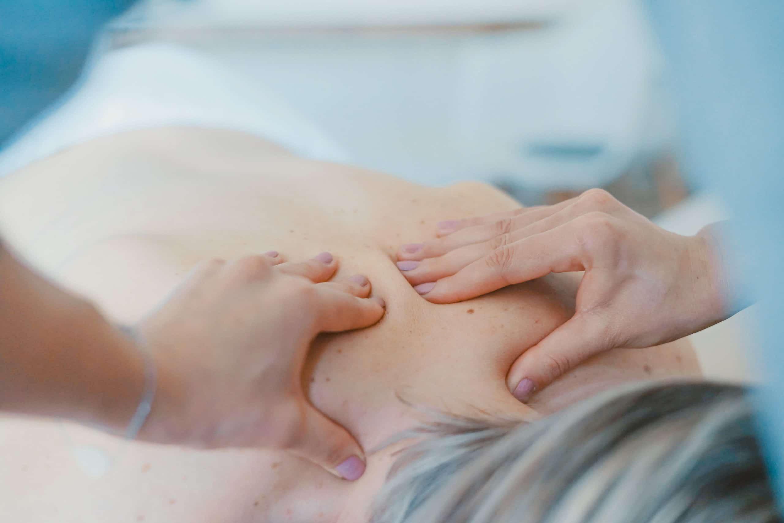 Mãos fazendo massagem nas costas de pessoa deitada vistos de cima