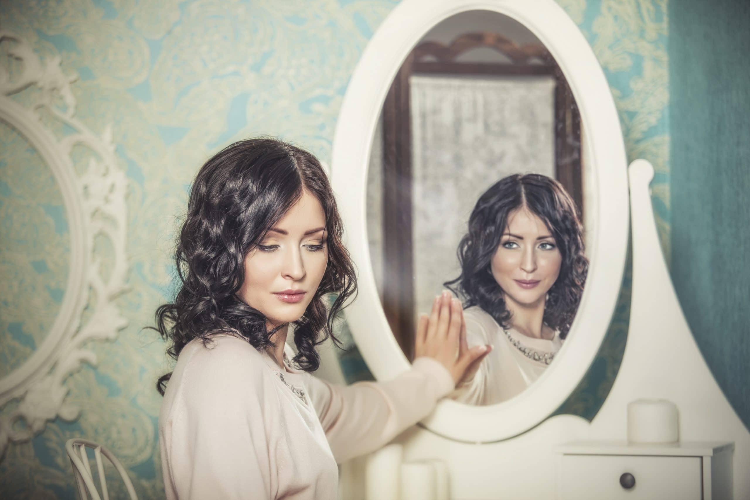 Mulher em frente ao espelho. Ela olha para trás enquanto o reflexo a observa.