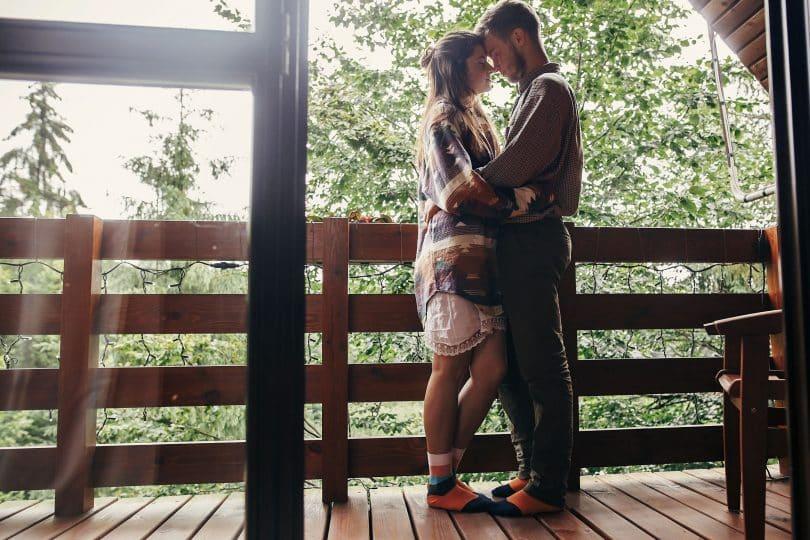 Casal relaxando na varanda, abraçando-se em uma cabana de madeira na floresta.