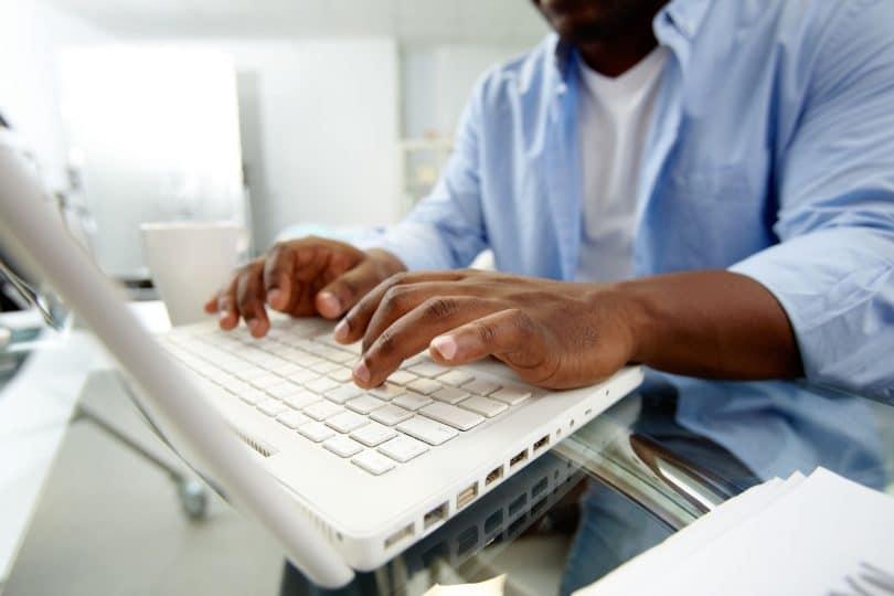 Mãos digitando em notebook