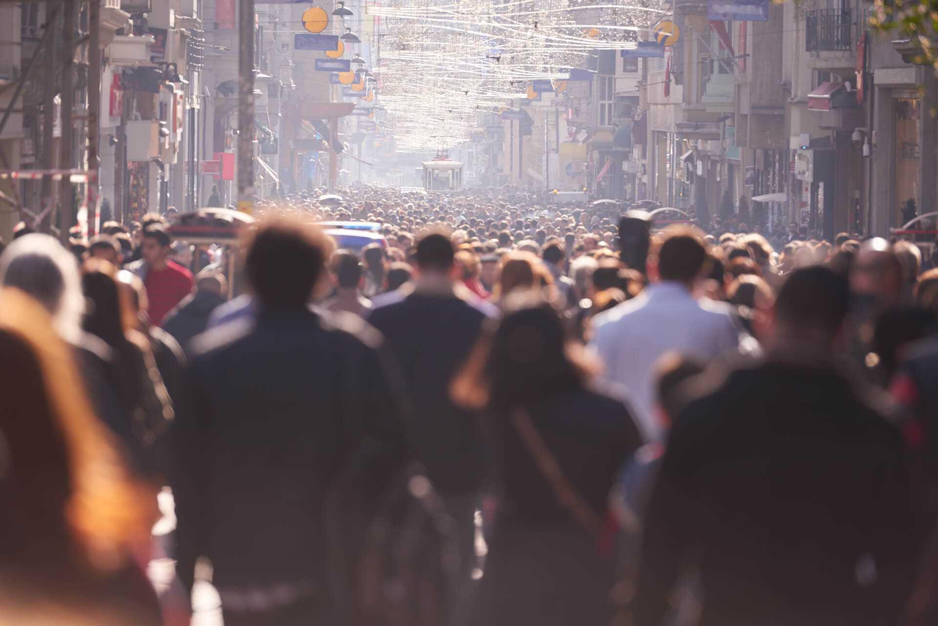 Multidão de pessoas andando na avenida de uma cidade.