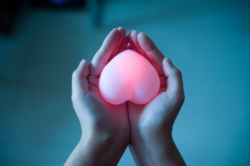 Uma mão de pele branca segurando um coração branco que brilha na cor vermelha.