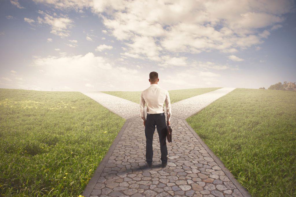 Homem vestido de social, parado em uma estrada de pedras que se divide em dois caminhos, representando uma tomada de decisão