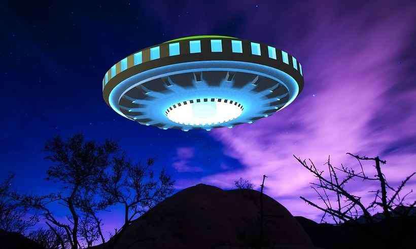 Disco voador sobrevoando a Terra durante a noite.