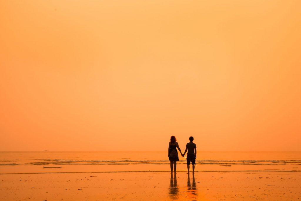 silhueta de duas pessoas caminhando na praia, de mãos dadas, no pôr do sol
