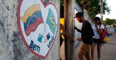 Muro com coração pintado com as bandeiras de Venezuela e Brasil pintadas escrito: Bem-vindos! E portão com pessoas entrando