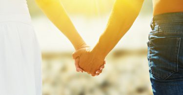 Silhueta das mãos de duas pessoas entrelaçadas enquanto caminham.