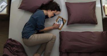 Mulher deitada na cama em luto com porta-retrato