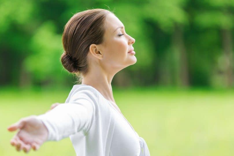 Mulher vista de lado com braços abertos e olhos fechados respirando fundo