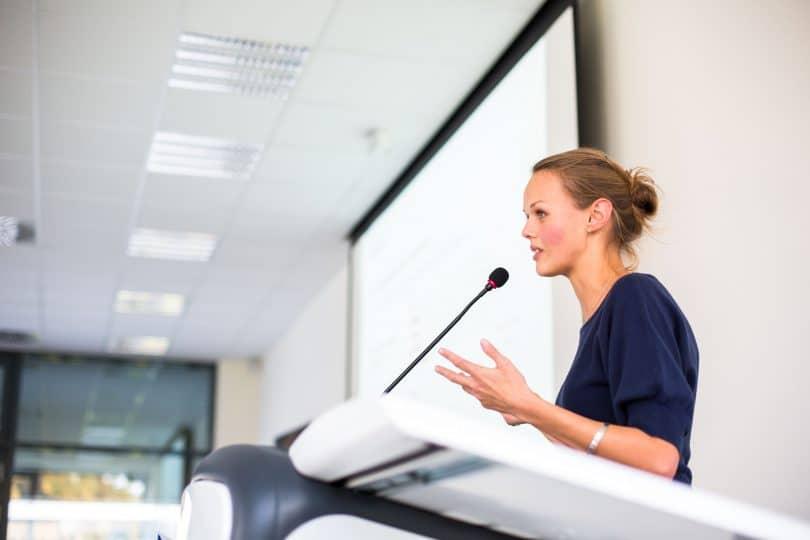 Mulher fazendo discurso no microfone.