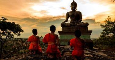 Três pequenos monges observando a estátua de um monge budista ao pôr-do-sol.