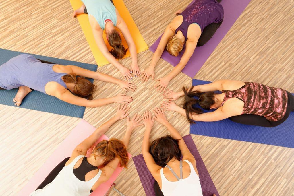 Grupo de seis mulheres vestidas em roupas de acadêmia, praticando yoga