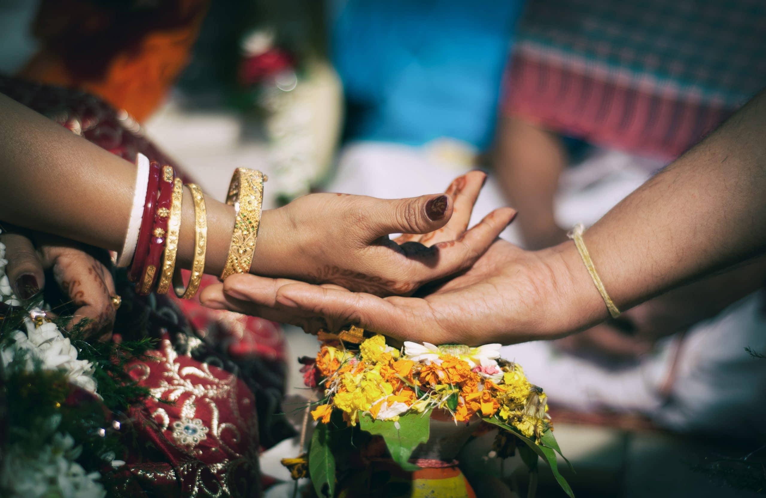 Uma mão segurando outra em um ritual de casamento indiano.