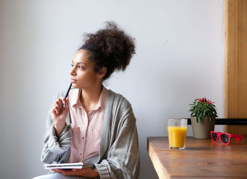 Mulher negra de cabelo preso, camisa rosa e casaco cinza. Ela está sentada ao lado de uma mesa com um suco e uma planta, com a caneta aproximada à boca e expressão de pensativa.