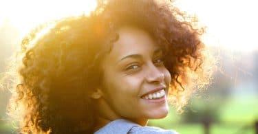 Mulher olhando de lado sorrindo com luz do sol ao fundo