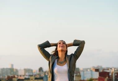 Mulher com mãos na cabeça e braços abertos sorrindo olhando para o céu com fundo de topos de prédios e céu