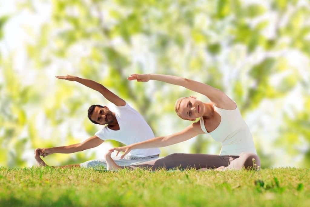 mulher branca jovem e homem moreno jovem, ambos vestindo roupas de ginástica, sentados na grama, praticando yoga
