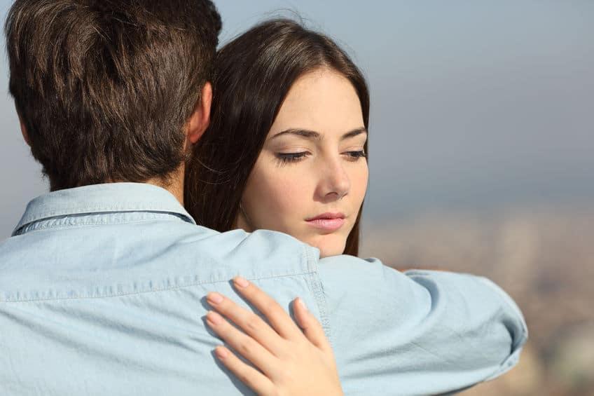 Mulher abraçando homem com desconfiança