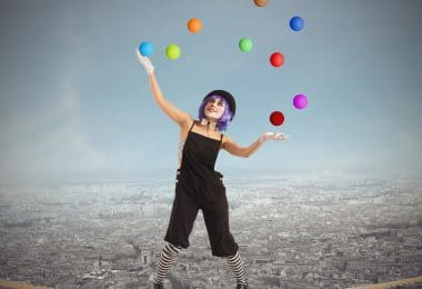 Palhaça se equilibrando em uma corda sobre a cidade.