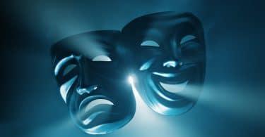 Duas máscaras de teatro com feições opostas sobre uma luz azul.