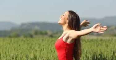 Mulher em campo verde com braços abertos sendo iluminada pelo sol