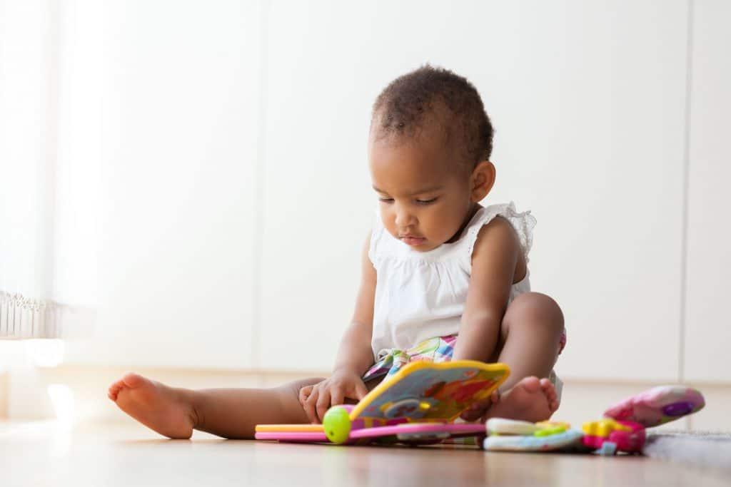 Bebê sentado no chão brincando com alguns brinquedos.