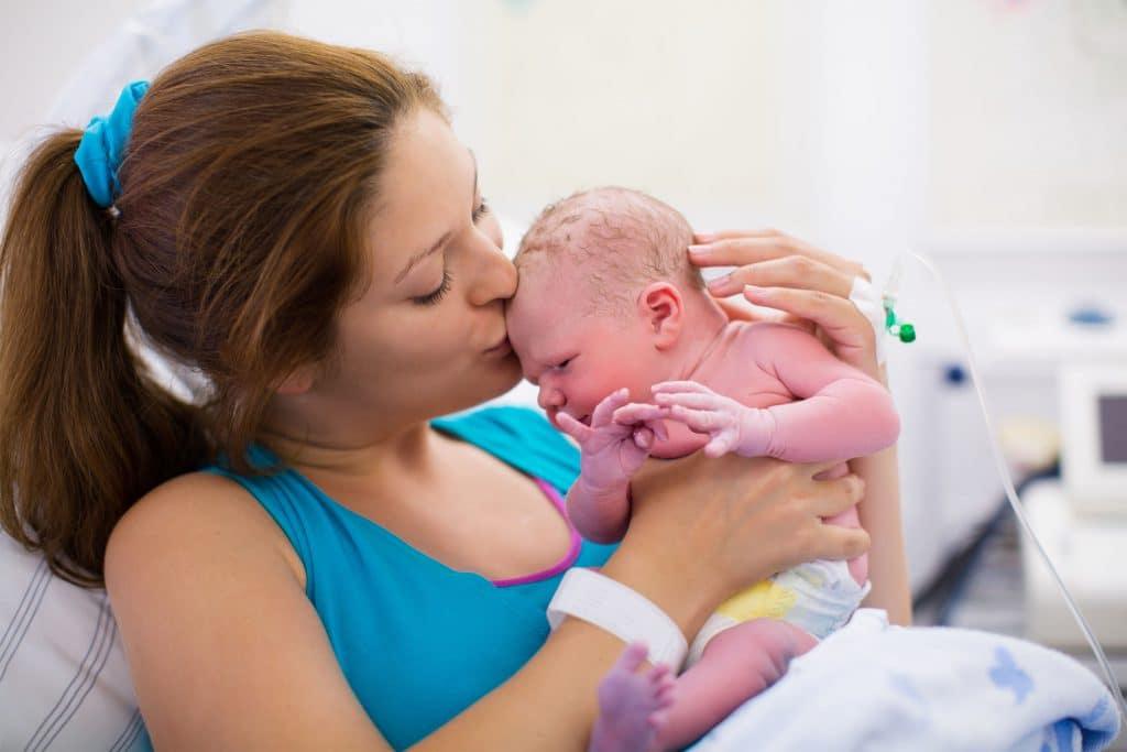 Uma mãe após trabalho de parto beijando a testa de seu filho que acaba de nascer.
