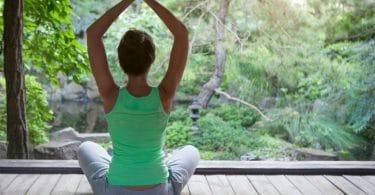 Mulher meditando sob piso de madeira, com um vidro separando-a de uma floresta