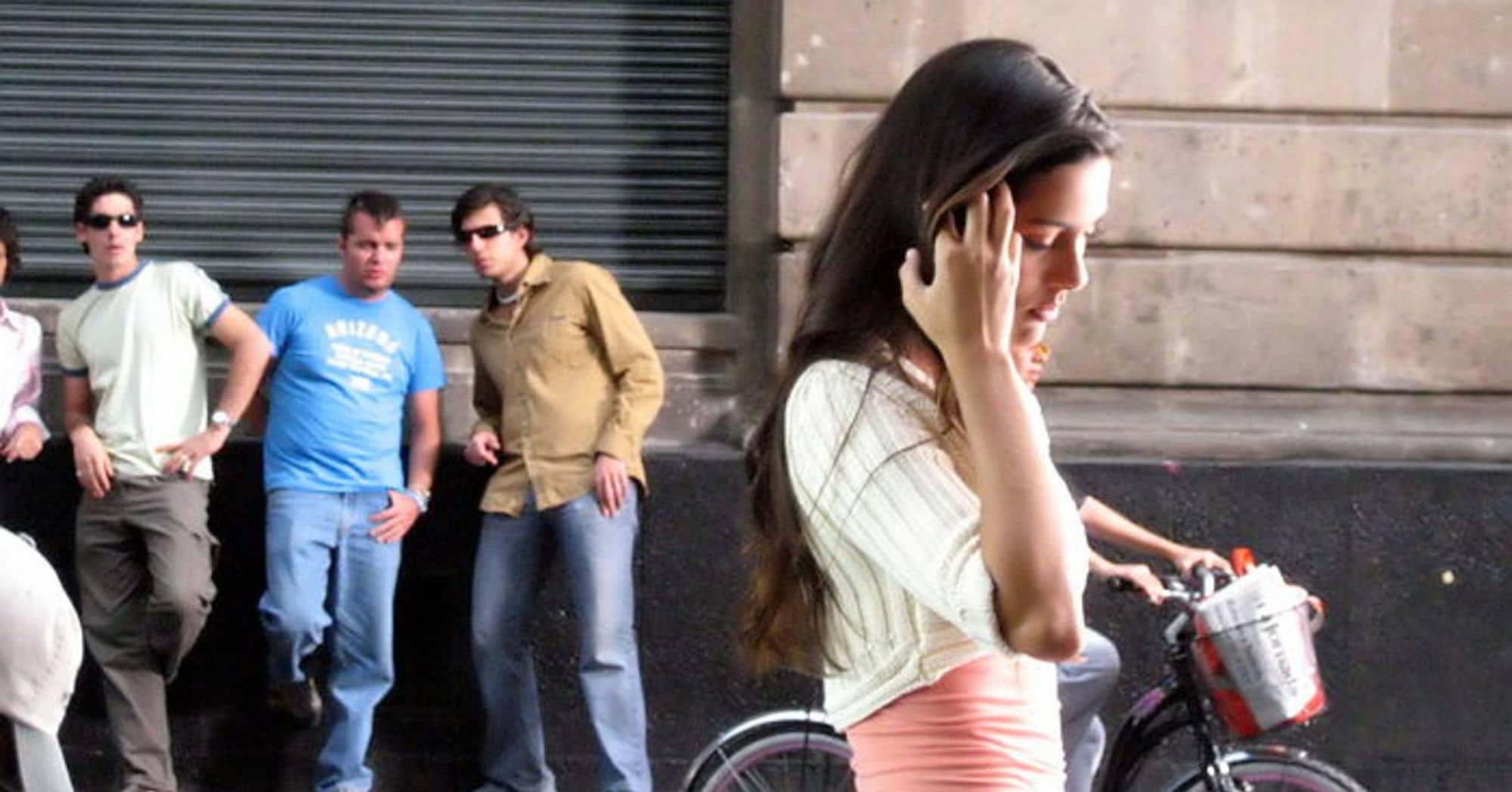 Mulher cobrindo o rosto ao andar na rua com três homens ao fundo a observando.