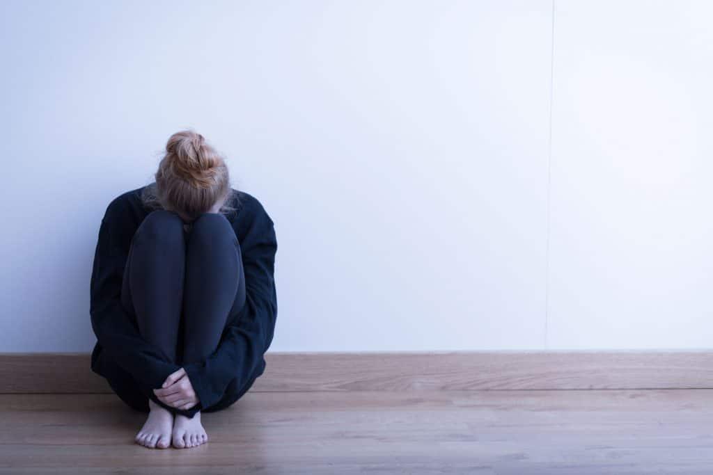 Mulher branca, jovem, sentada no chão, escondendo sua cabeça entre as pernas, com as costas apoiadas em uma parede branca.