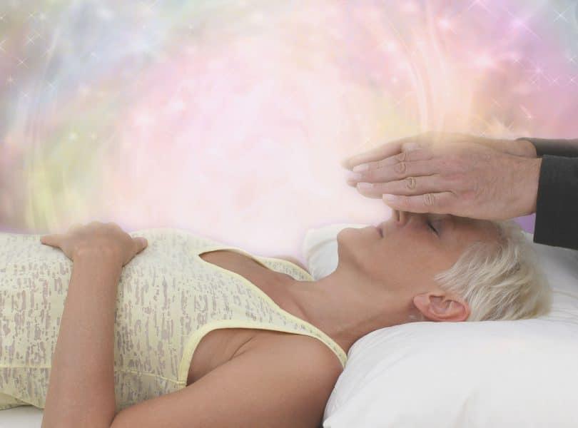 Uma mulher de regata está deitada e, acima de seu rosto, há uma mão.