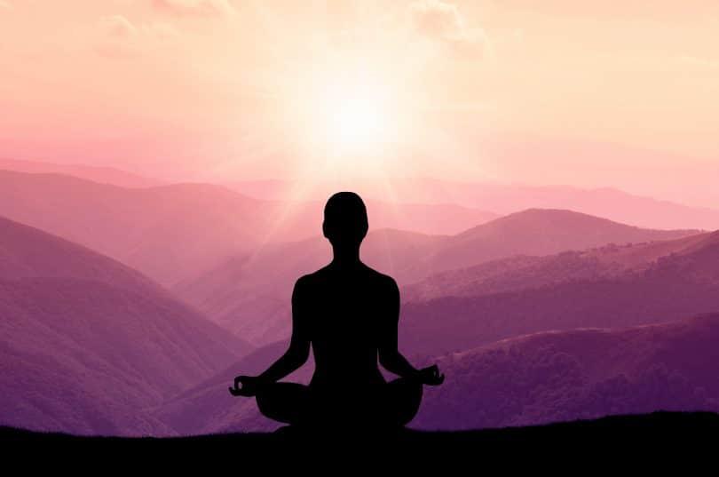Silhueta de uma pessoa de costas meditando com o sol e montanhas ao horizonte.