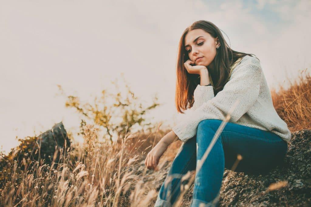 Mulher negra sentada sobre a grama em uma tarde ensolarada. Ela usa um moletom branco e uma calça jeans, apoiando sua cabeça em sua mão e demonstra estar pensativa.