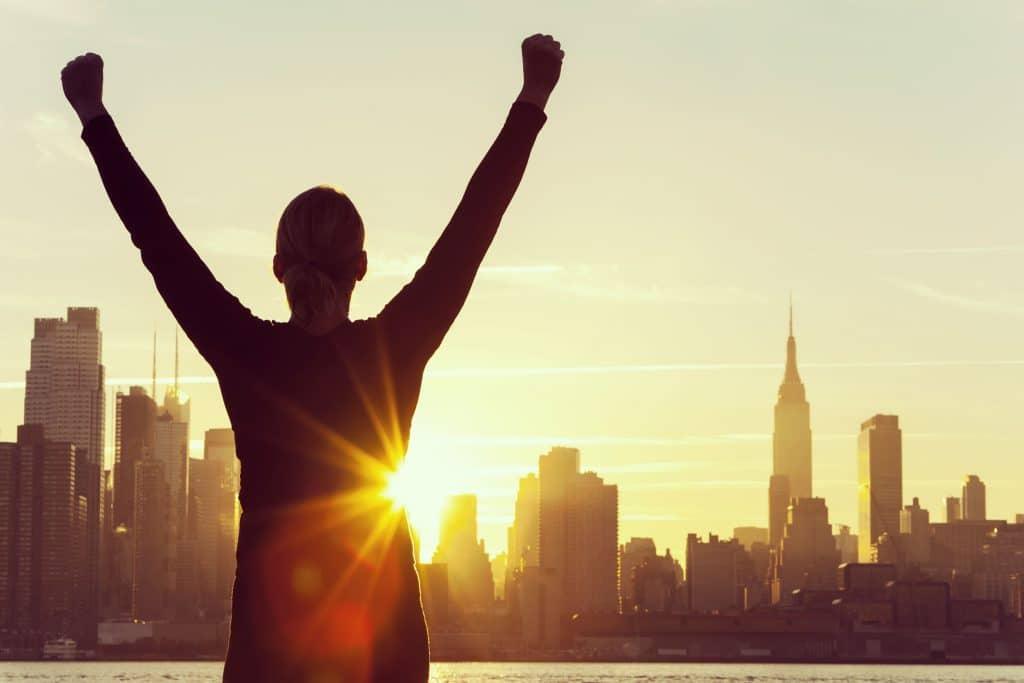 Silhueta de mulher com os braços para cima, em sinal de vitória, observando uma paisagem urbana