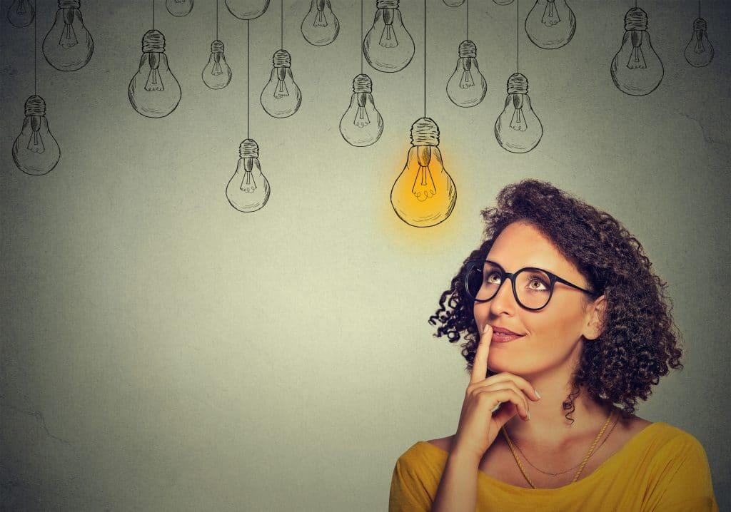 Mulher de óculos de grau com armação preta, pele negra e uma blusa amarela. Ela olha pra cima com o dedo encostado na boca, direcionando o olhar para ilustrações de lâmpadas que representam ideias.
