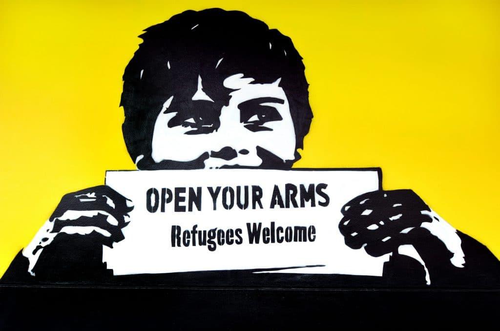Ilustração de grafite de criança segurando cartaz escrito em inglês: abra seus braços e receba os refugiados