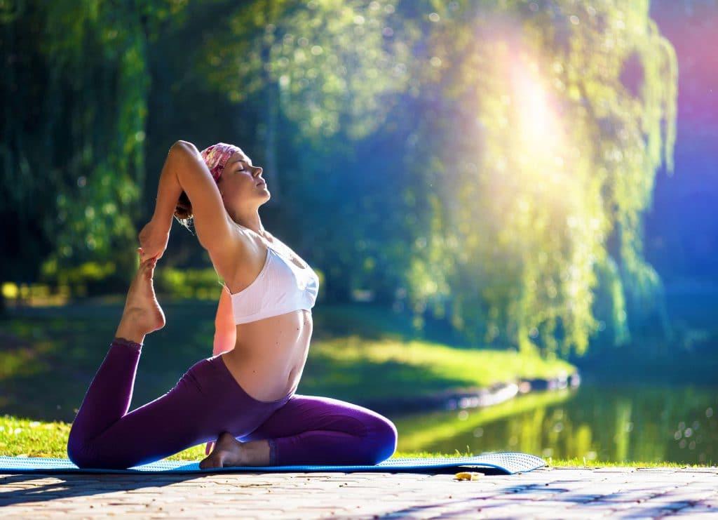 mulher jovem, bronzeada, praticando yoga na natureza, em frente à um lago, em um dia ensolarado