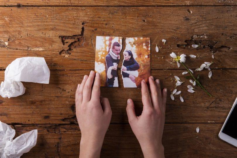 Mãos de pessoa branca segurando uma foto de casal rasgada ao meio, em cima de uma mesa de madeira, representando o término de relacionamento.