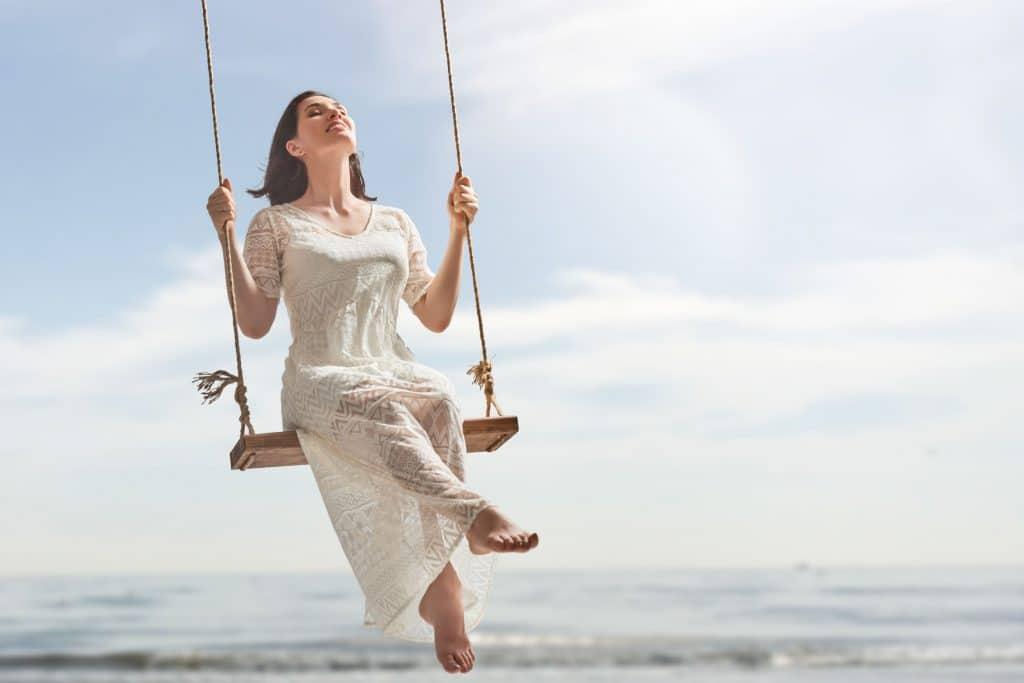 Mulher branca, vestida de branco, sentada em um balanço na praia, sorrindo e tomando sol
