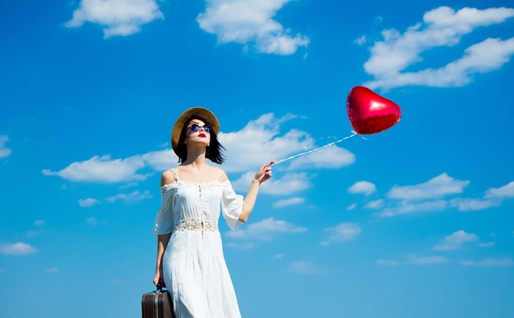 Mulher branca de cabelo liso e preto, com um vestido longo branco, um óculos escuro e batom vermelho. Ola usa um cpéu marrom, com uma mãe carrega uma mala e com a outra, segura um balão vermelho em forma de coração.