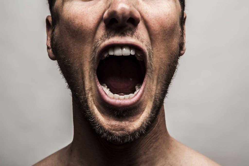 foto cole do rosto de um homem branco, jovem, gritando de ravia
