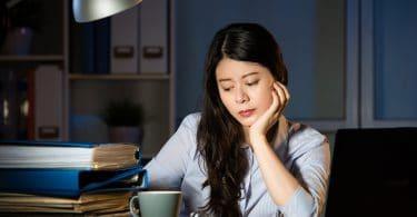 Mulher sentada em uma mesa de escritório, cabisbaixa, atrás de uma pilha de livros e um notebook.