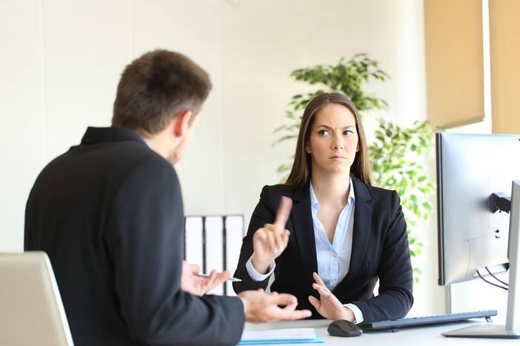 Homem e mulher, ambos brancos, vestidos de social, em um escritório. Mulher sentada atrás de uma mesa, falando não, gesticulando com a mão, para o homem que está sentado na sua frente.