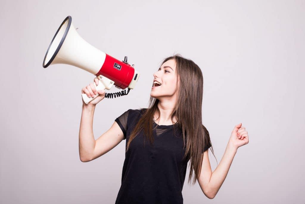 Mulher com camiseta preta segurando um alto falante na mão e simulando uma fala.