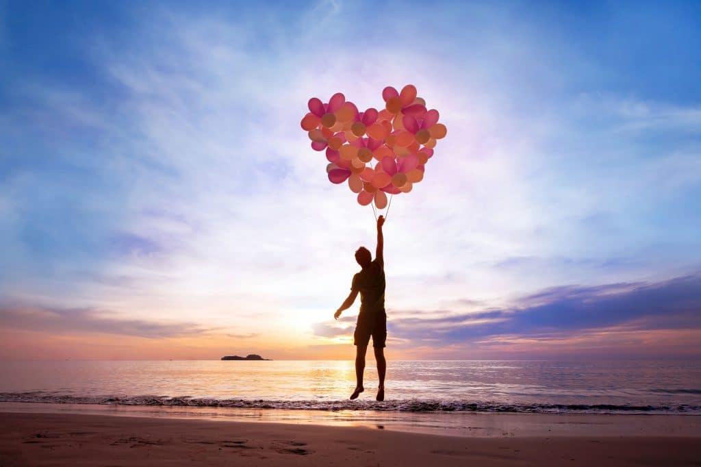 Silhueta de pessoa na praia sendo levantada por vários balões entrelaçados, formando um coração