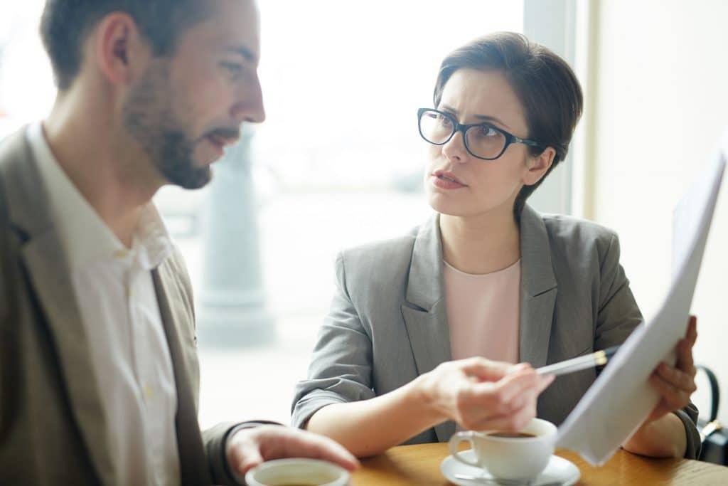 Mulher e homem, ambos vestindo roupas sociais, sentados em uma mesa, tomando café e conversando sobre um documento que está na mão da mulher