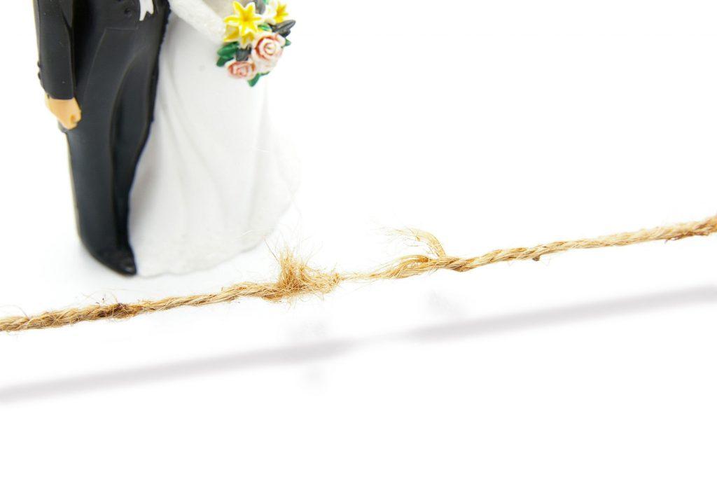 bonecos de topo de casamento, colocado em cima de uma mesa branca, ao lado de uma corda prestes a se romper
