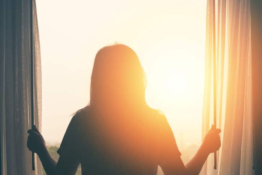 Mulher olhando pela janela ao amanhecer